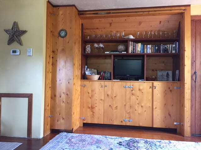 Handmade, reclaimed yellow cedar cabinetry lining the living room wall is especially beautiful.
