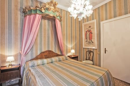 Master Bedroom, wooden cut bed crown painted in gold and skills on the walls. The most classic Venetian bedroom!