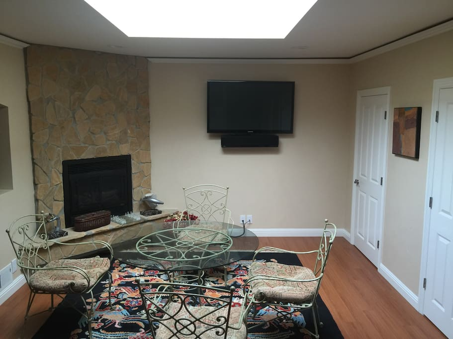 """Fireplace in dining room along with 60"""" diagonal tv and large skylight to brighten up the entire dining area."""