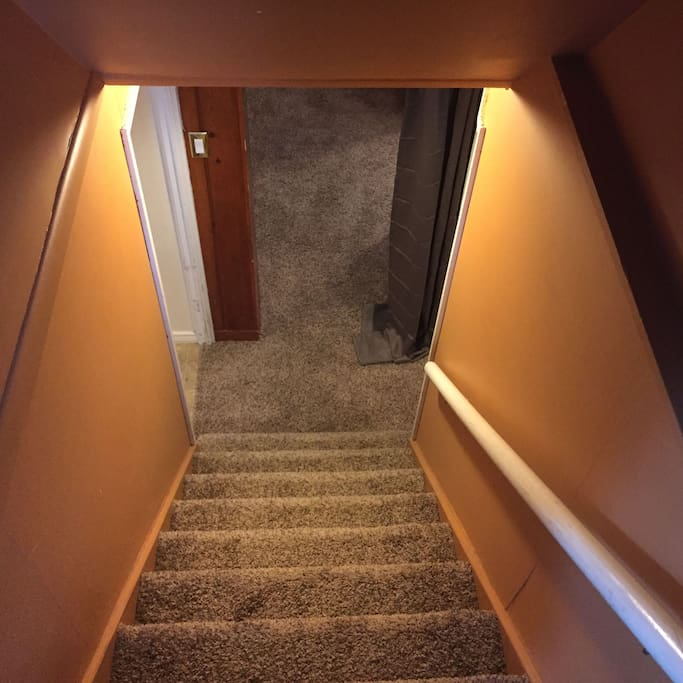 Stairs leading down to the listings bedrooms, bathroom and living area.