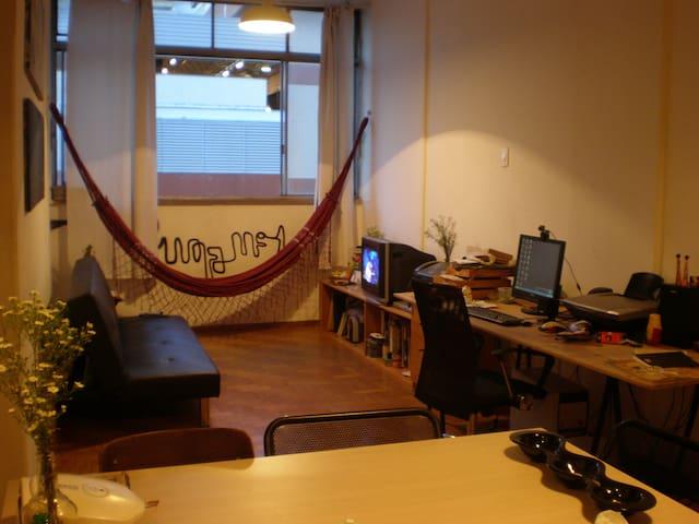sala com sofá cama, mesa de escritório e rede