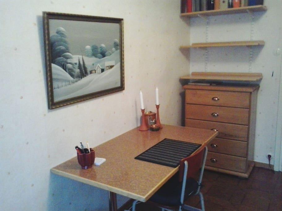 Skrivbord med plats för dator, stor byrå och garderob.