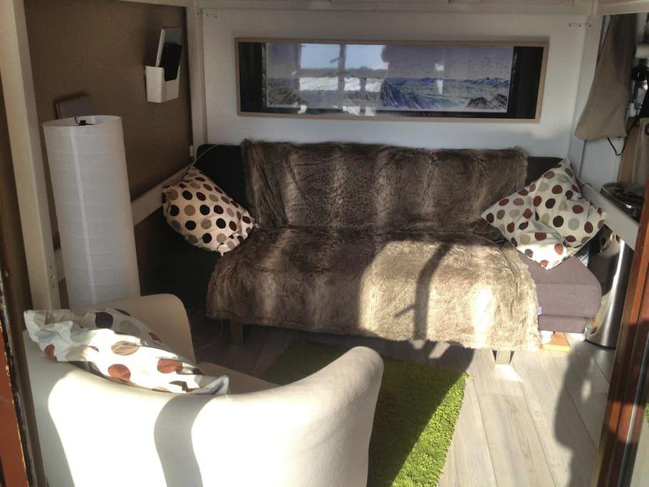 Salon confortable, avec table à roulette sous le sofa, 2 poufs coffres