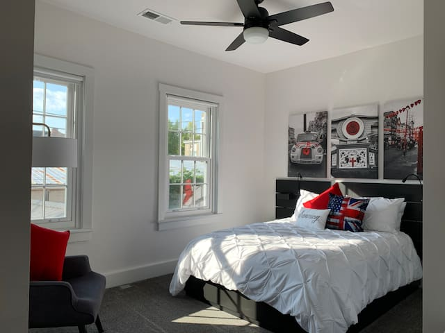 London themed room with reading lights and USB ports on both sides, along with remote control fan and room darkening shades; echo dot alarm clock as part of the Alexa system throughout the home.