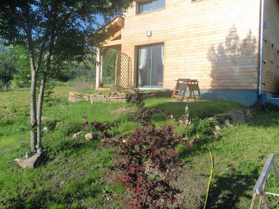 La vue sur la terrasse et jardin devant le studio (avec sa baie vitrée)