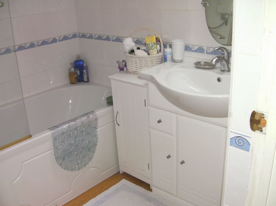 Clean bathroom with electric shower over the bath.