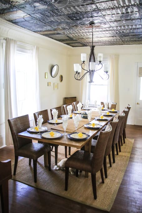 Formal dining room seats 12 on beautiful hand made wooden dining set. Freshly uncovered original tin ceiling.