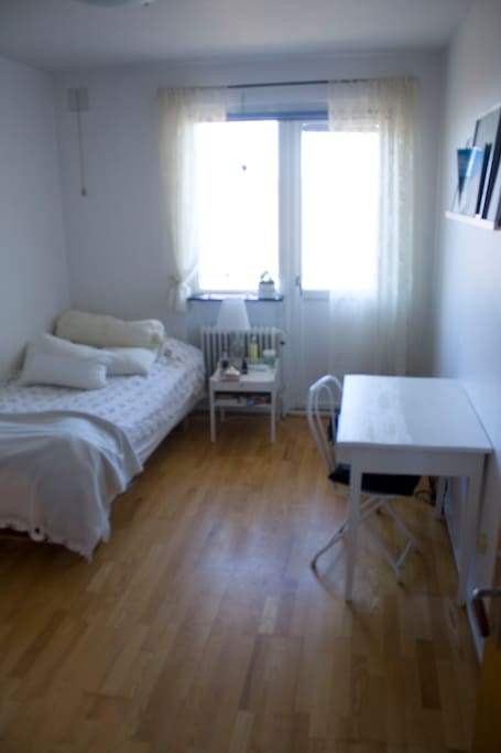 Bedroom with a comfortable bed and the balcony door and balcony where you can sit and enjoy your morning coffee.