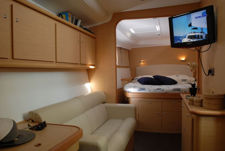 Cabina armatoriale spaziosa con televisore, divano, armadi e cassettiere.