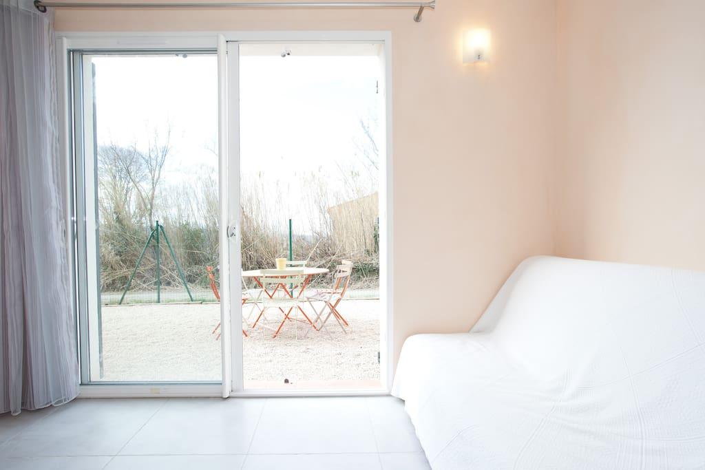 Banquette convertible dans cuisine 20 m² avec porte-fenêtre donnant sur terrasse privative et tonnelle de 40 m²