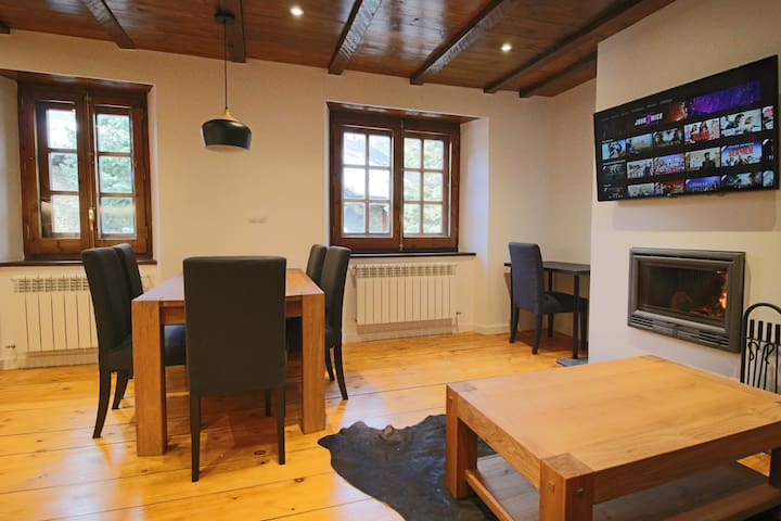 Spacious living-room with wooden chimney and smart tv connected to netflix and amazon prime.