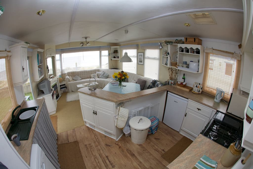 Bright and airy living / dining room and kitchen with uninterrupted sea views and access to beach