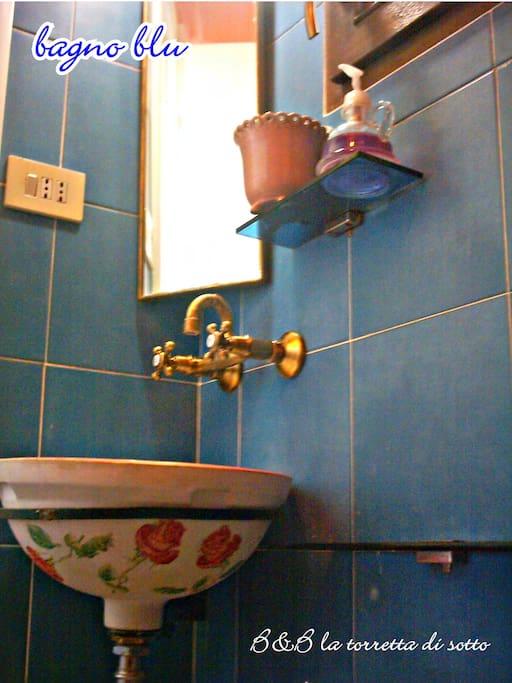 il bagno azzurro della suite Artemisia con doccia, shampoo, sapone, asciugamani e teli bagno