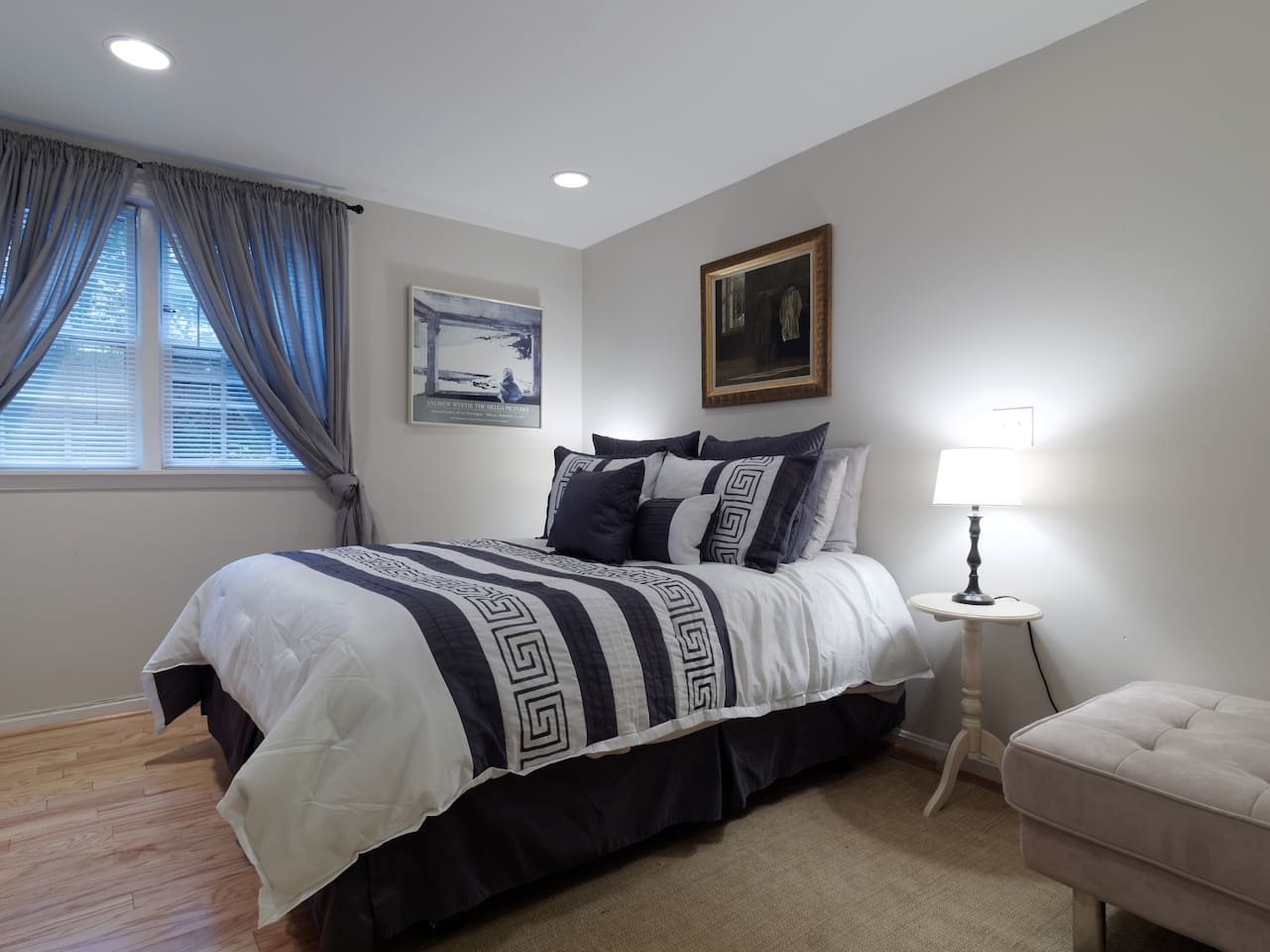Bedroom with queen sized bed, ottoman, full closet.
