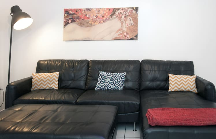 Large couch in the living room, perfect for relaxing and watching the flat screen TV, or providing sleeping for 2