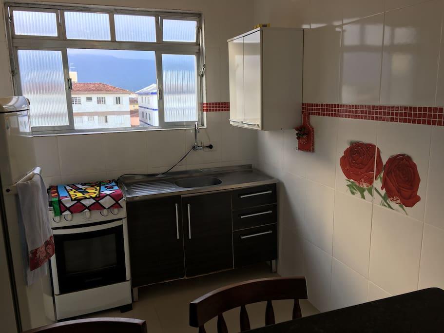 Cozinha com boa ventilação, geladeira, gabinete e pia, fogão com botijão de gás, armários suspensos, pratos, copos e talheres.