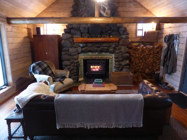 A woodstove, ample supply of firewood, and cozy throw blankets promise to warm wintry nights.