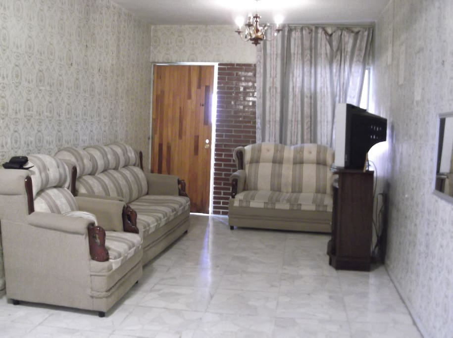 Clean, white tile floors and plenty of comfortable seating in living room on second floor