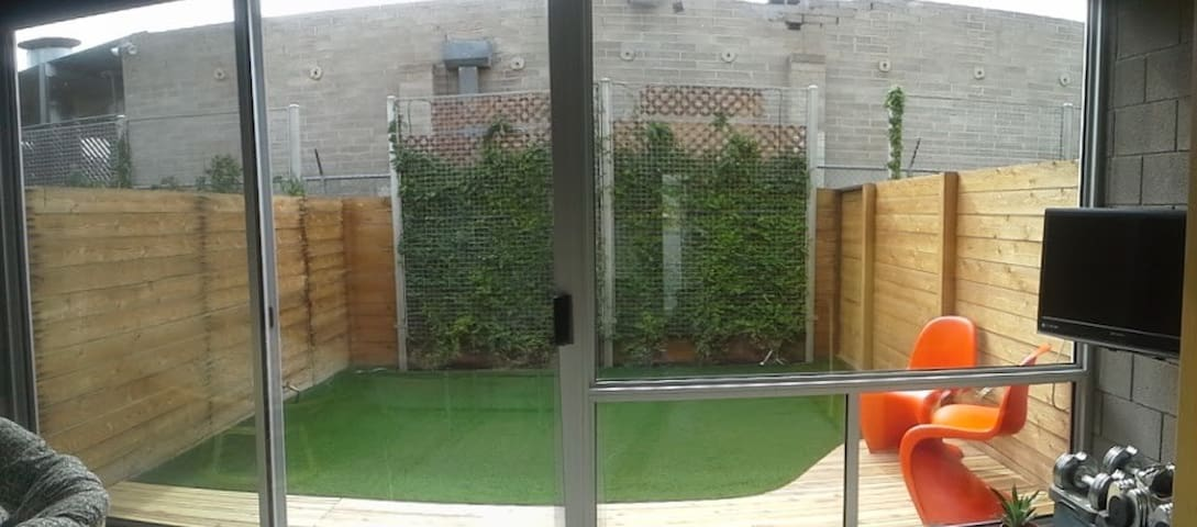 Daytime shot of backyard. The windows have full roller shades that can be closed to block out 97% of light