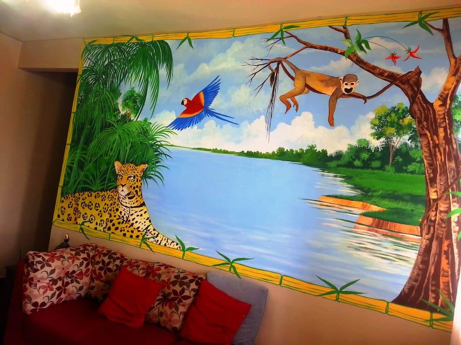 Sala com pintura regional de onça, macaco e arara