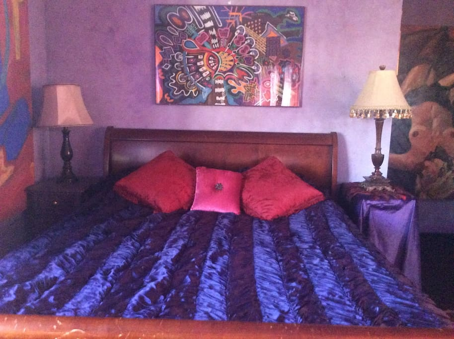 Queen bed, two paintings by Dragon Sundancer and one by Jeffery Fine.