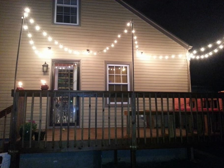 Relaxing back deck with bench seating, fire pit, and hanging lights.