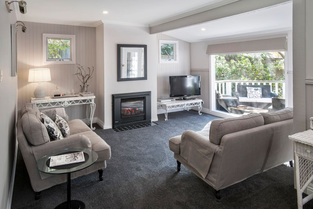 Lounge with gas log fire, air conditioning & large picture window overlooking the garden.