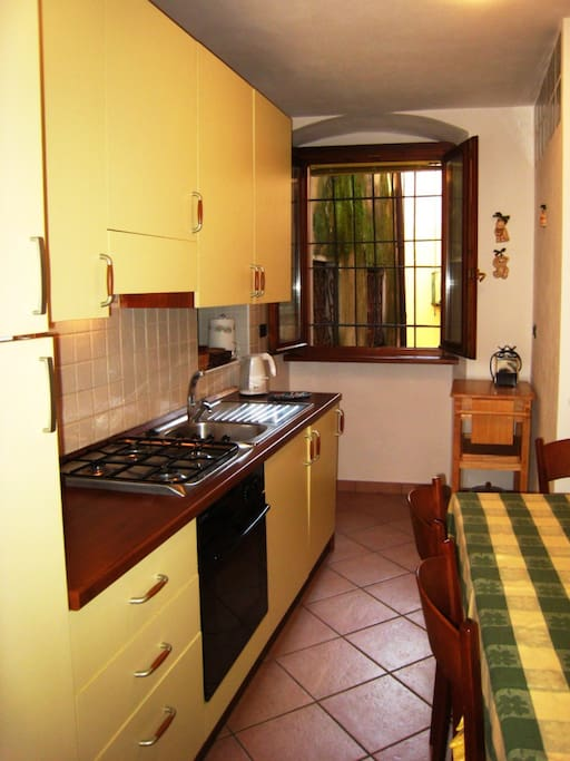 Fully fitted kitchen with dishwasher, and dining table for six, with kitchen window overlooking Via Prestinari