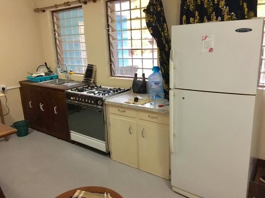 Full kitchen with fridge, gas stove, sink, small microwave, coffee machine and utensils