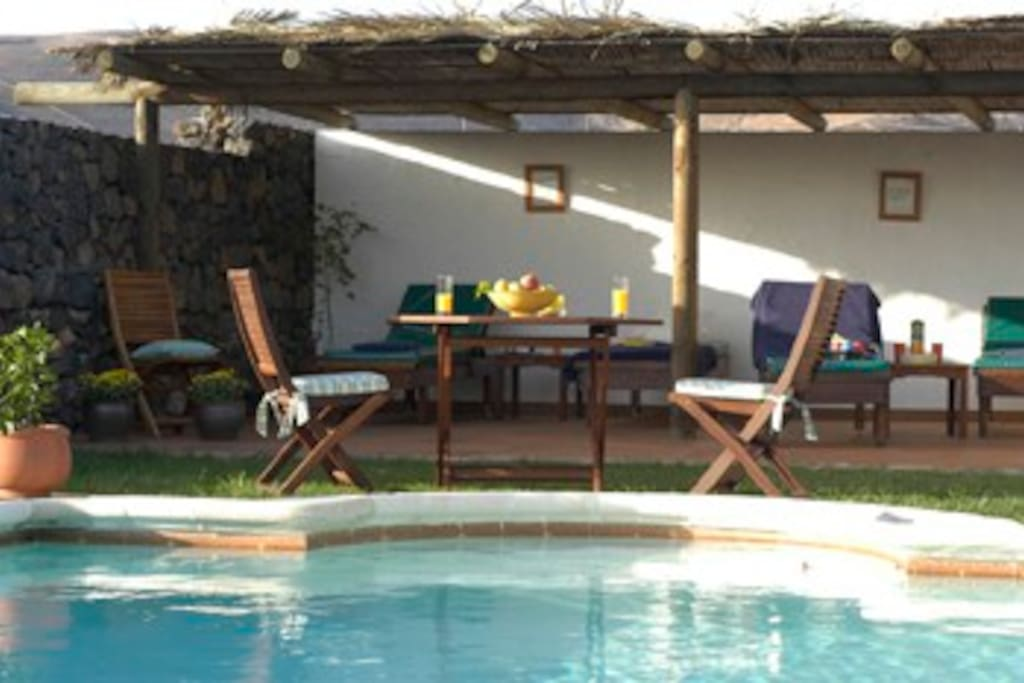Breakfast table and sunbeds by the heated pool