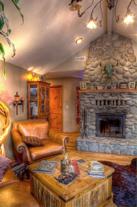 Fully functional stone fireplace and incredible chandelier in main living room.
