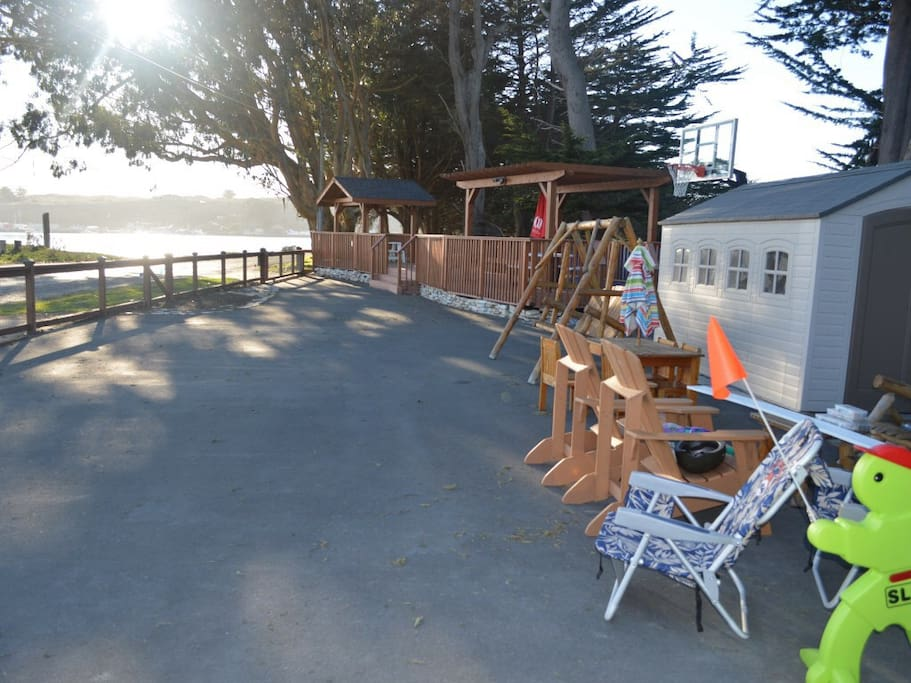 Front yard with basketball system and large deck overlooking the bay.