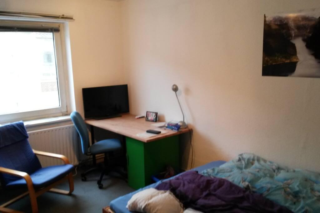 Schreibtisch mit Blick auf Fernseher und aus dem Fenster