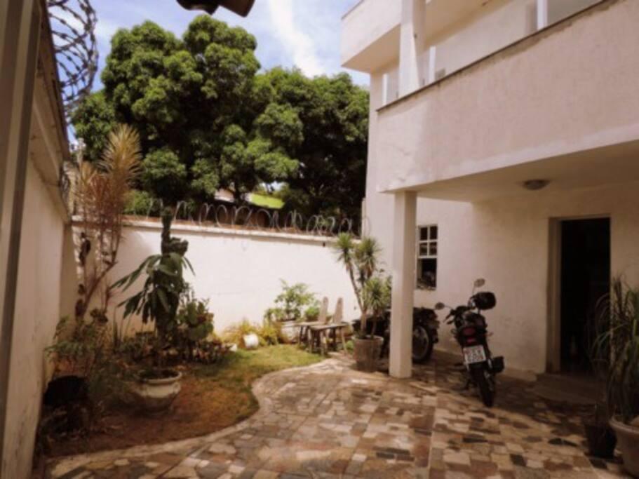 Casa ampla com espaço para churrasco e área verde.