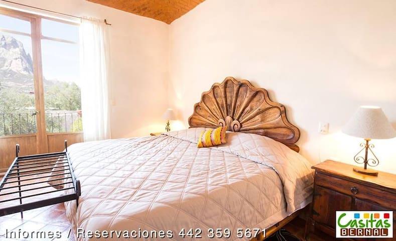 Habitación con cama king y terraza con vista a la peña