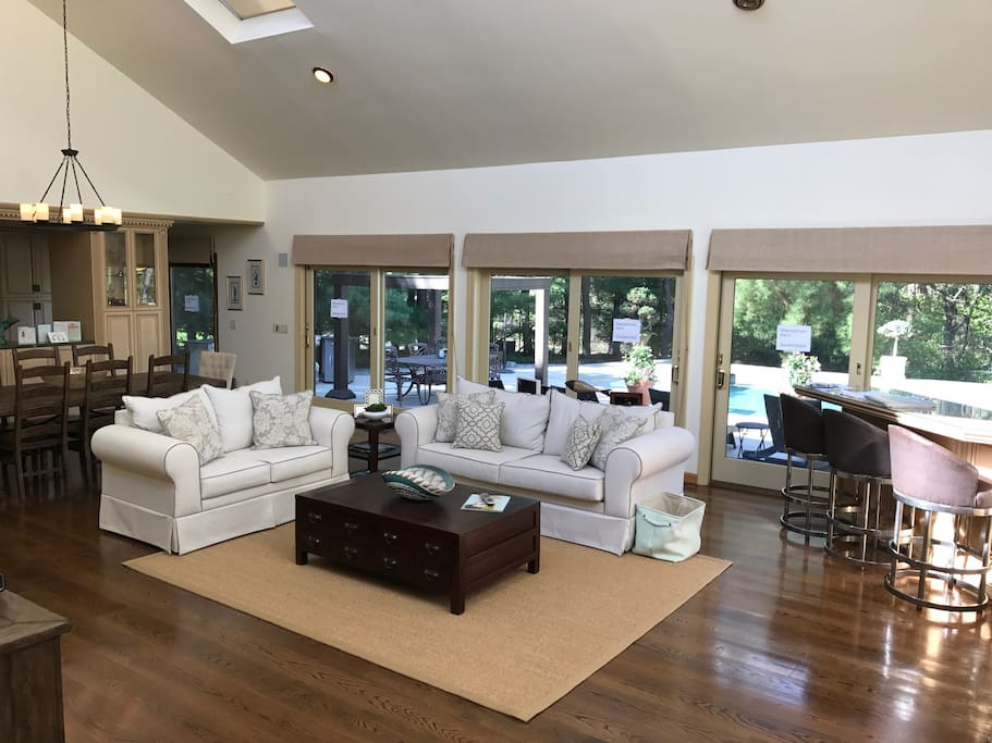 Open living room/dining room with flat screen TV, high ceilings and sky lights that open directly to pool deck.