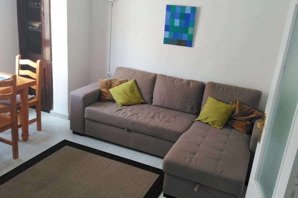 Living room with corner sofa/sofabed, extendible dining table with four chairs.