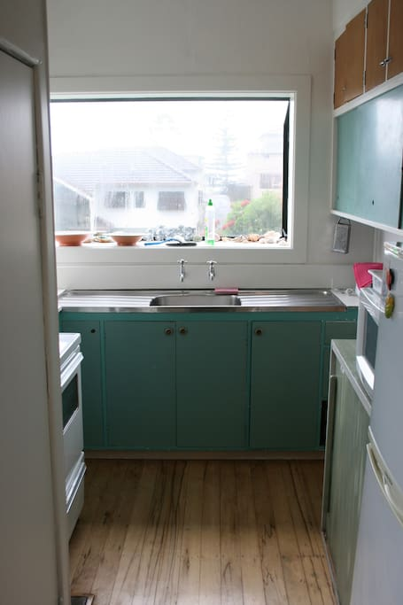 This is the Kitchen, equipped with fridge, microwave, stove, plates , pots etc