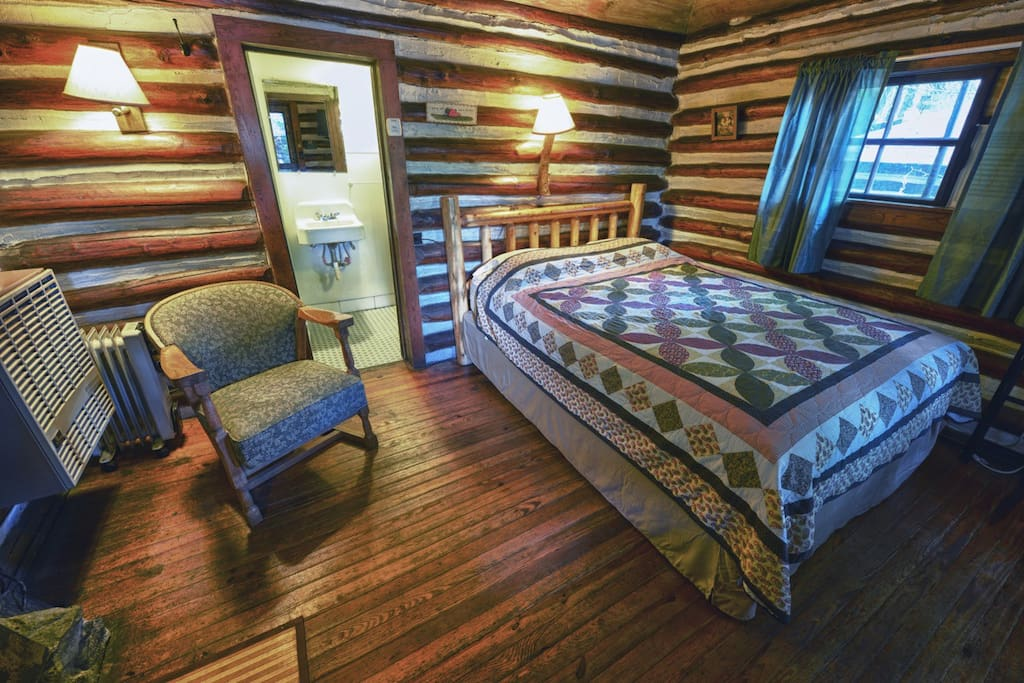 Interior of Hill Billy cabin.  Queen bed, chair, gas furnace, wood burning fireplace, bathroom.