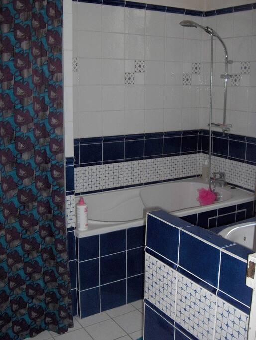 Salle de bains spacieuse avec lave-linge, grande baignoire, rangements