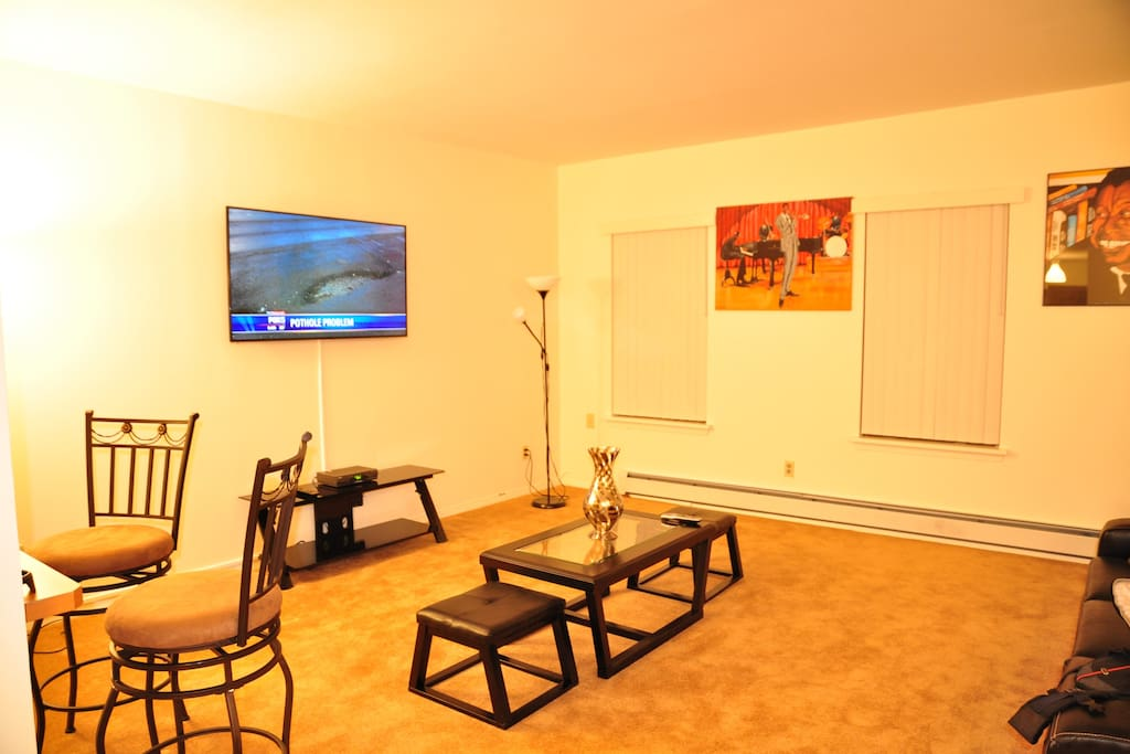 """The Living Room: It is spacious and comfortable with high ceilings, up-to-date leather furnishings(which also doubles as an extra sleeping space with a pull-out bed), as well as a wall mounted 60"""" flat screen television with free 24 hour cable access for"""
