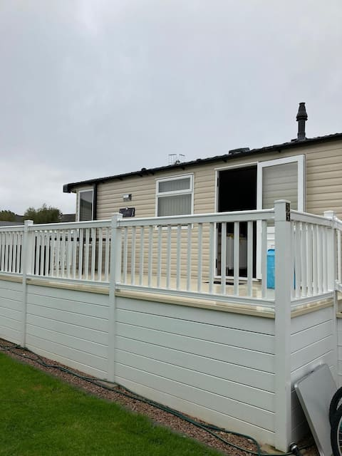 Delightful 3 bed holiday home on a Riverside holiday park, sleeps upto 8 persons with 2 toilets and shower central heating, outdoor eating/lounge area on raised decking at same level as home. clubhouse/restaurant short walk over footbridge.