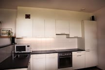 A fully equipped open kitchen with dishwasher and oven
