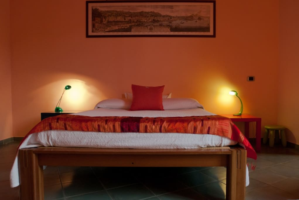 The double bed in the red room that can host up to 3 persons.
