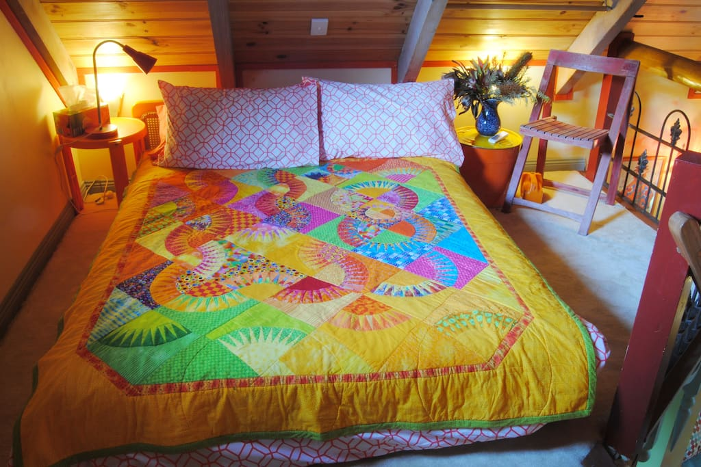 A beautiful, vibrant handmade quilt  and fine linen on a double bed in the loft. The bed is on a low wooden frame but comfortable and with room to stand under the high rafters and a spacious feel .