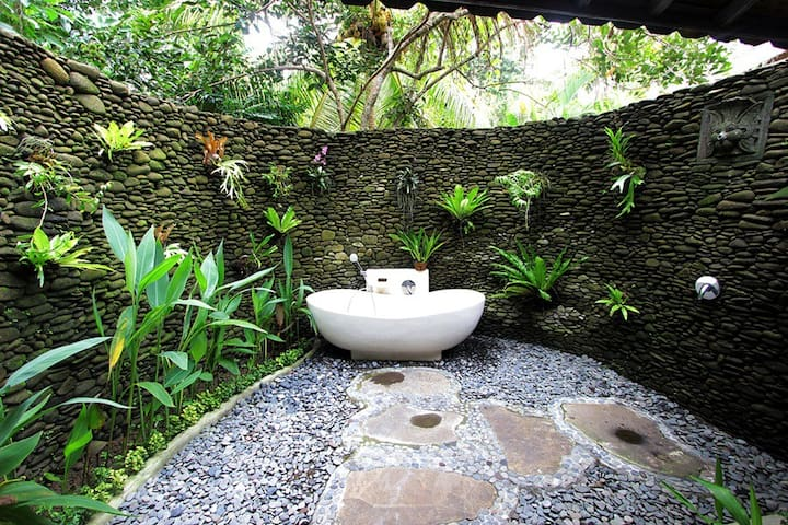 Private garden outdoor bathroom with tub, shower, beautiful stonework and tree shade