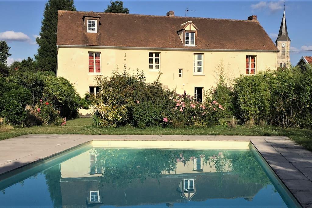 La piscine devant la maison séparée d'une haie végétale