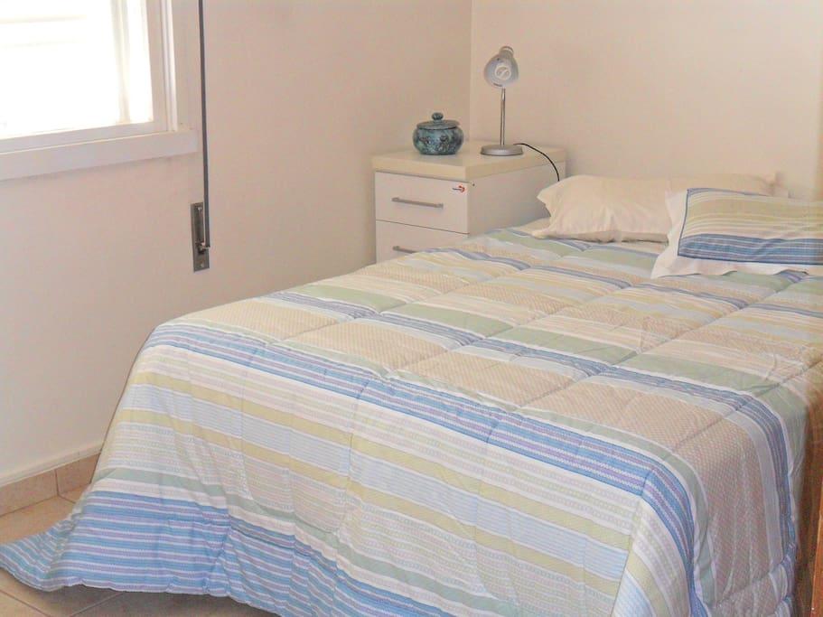 Quarto com cama de casal com colchão de molas Herval, bem arejado e com ótima luz natural, pega o sol da manhã. De fundos e muito silencioso.