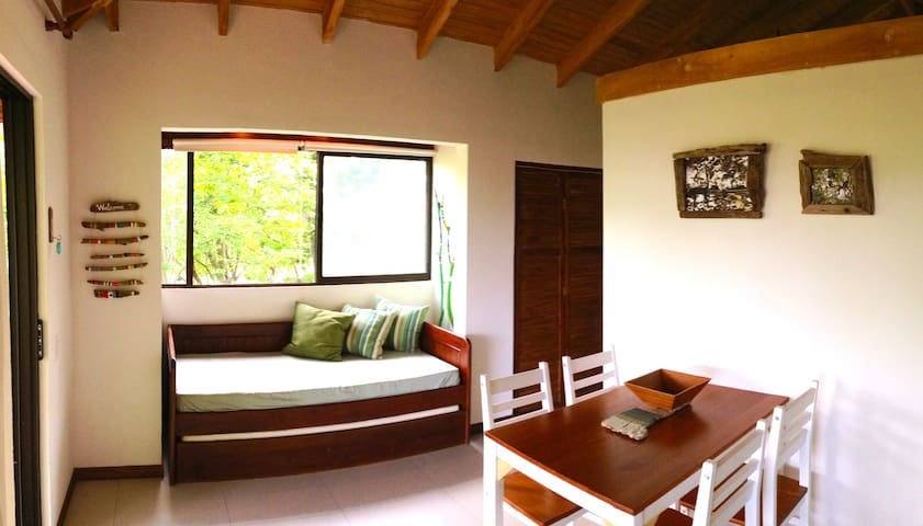Showing you the comfy, bright daybed area where you can look out to the pool and the gardens.