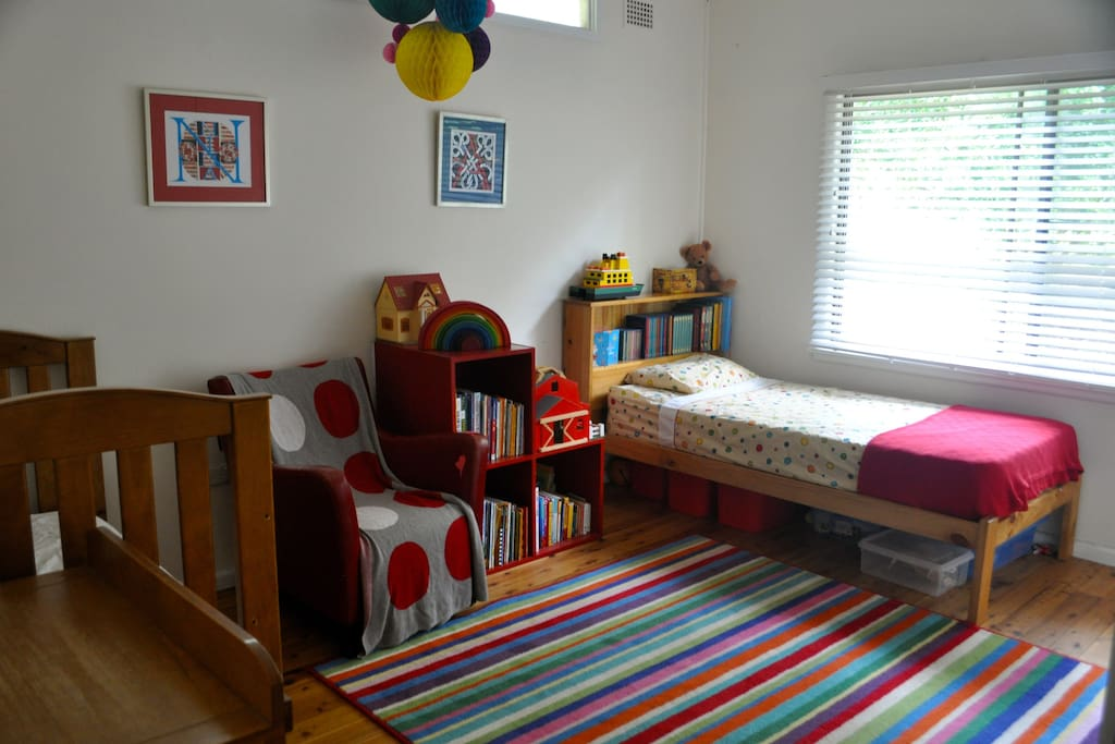 Large, light bedroom with a single bed and cot.